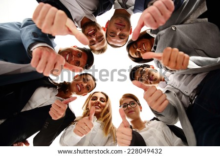 Group of business people standing in circle, with thumbs up - stock photo