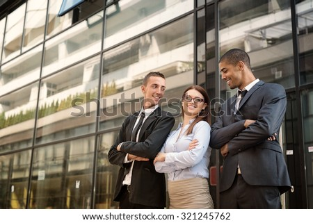 Group of business people standing in front of a glassy building, looking each other and smiling. - stock photo