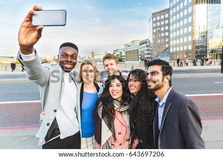 Group of business people taking a selfie in London. Mixed race group of people with Tower Bridge on background. Travel and lifestyle concepts.
