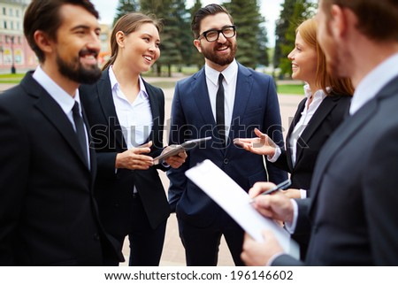 Group of business people talking at meeting outside - stock photo