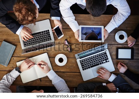 Group of business people using modern gadgets at workplace - stock photo