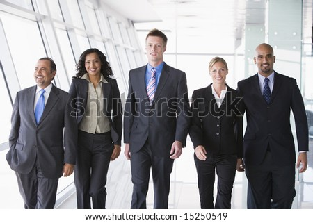 Group of business people walking through office towards camera - stock photo