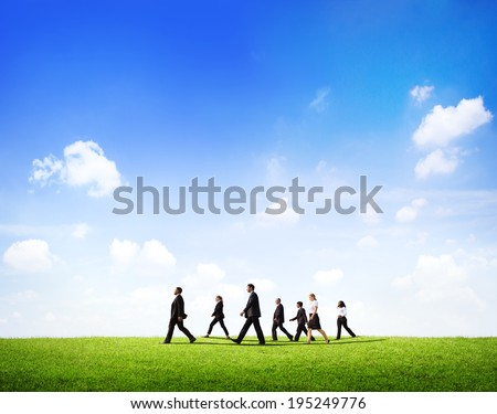 Group Of Business People Walking Through The Field In Daylight. - stock photo