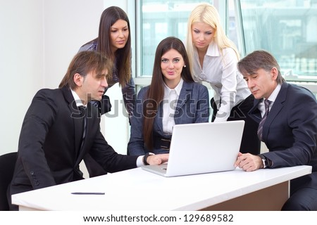 Group of business people working in the office on laptop and congratulating office co-worker on job well done