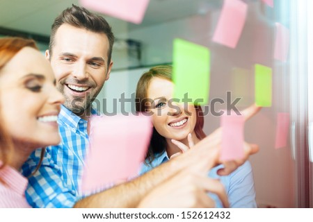 Group of business people working on new project with many sticky notes on window - stock photo