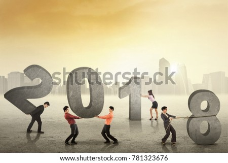 Group of business team trying to arrange numbers 2018, symbolizing of working together for the future
