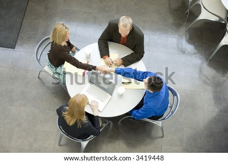 Group of businessmen at a table shake hands - stock photo