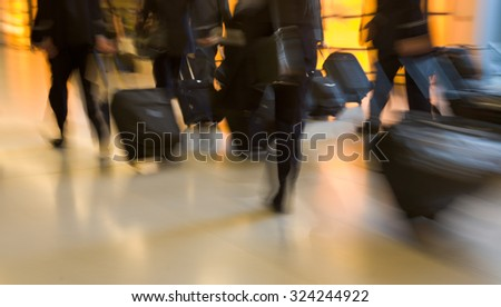Group of businessmen carrying luggage in the airport, strong motion blur - stock photo
