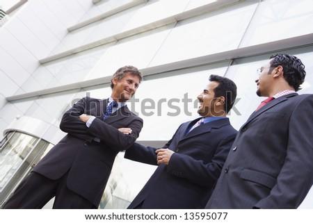 Group of businessmen outside modern office building - stock photo