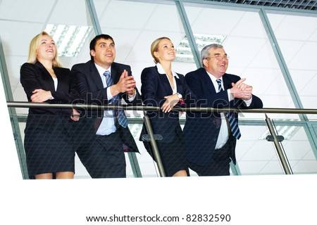 Group of businesspeople and their senior boss standing by banisters - stock photo