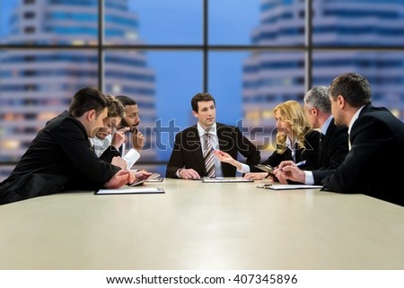 Group of businesspeople at table. Evening discussion in business center. It was a long day. Moving closer to consensus. - stock photo