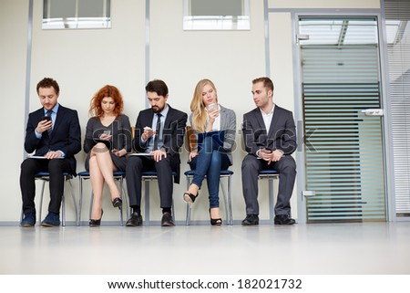Group of businesspeople busy with their smartphones  - stock photo