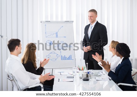 Group Of Businesspeople Clapping For Businessman After Presentation - stock photo