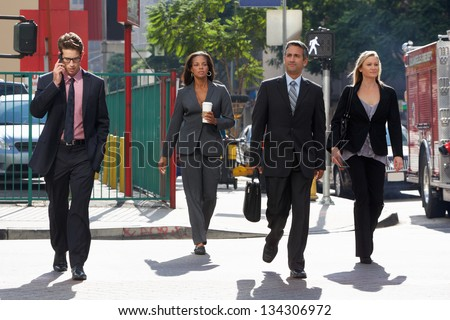 Group Of Businesspeople Crossing Street - stock photo