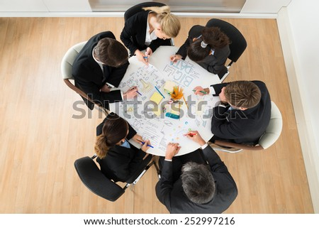 Group Of Businesspeople Discussing At Meeting In Office - stock photo