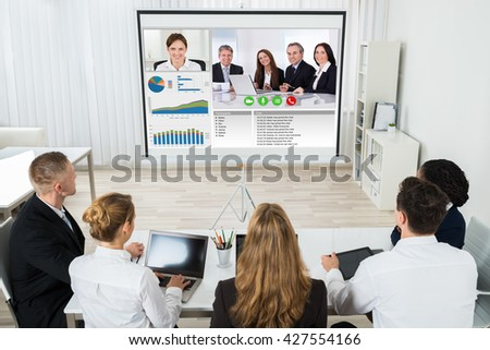 Group Of Businesspeople Discussing Graphs Through Videochat In Office - stock photo