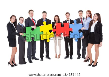 Group of businesspeople holding four large brightly colored puzzle pieces conceptual of teamwork in solving a business problem or meeting a challenge  isolated on white - stock photo