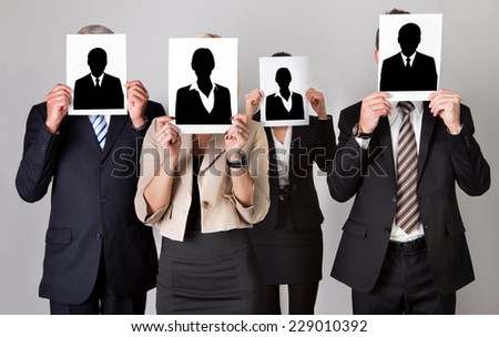 Group of businesspeople holding photographs in front of faces against gray background - stock photo