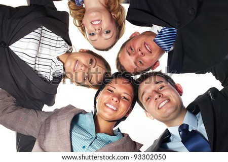 Group of 5 businesspeople in a circle looking down, unity and teamwork concept, low angle shoot