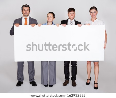 Group Of Businesspeople In A Row Holding Placard - stock photo