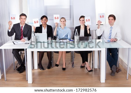 Group Of Businesspeople In Conference Holding Voting Paper - stock photo
