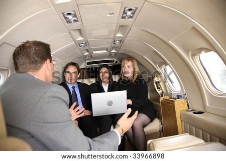 Group of businesspeople meeting in private jet - stock photo