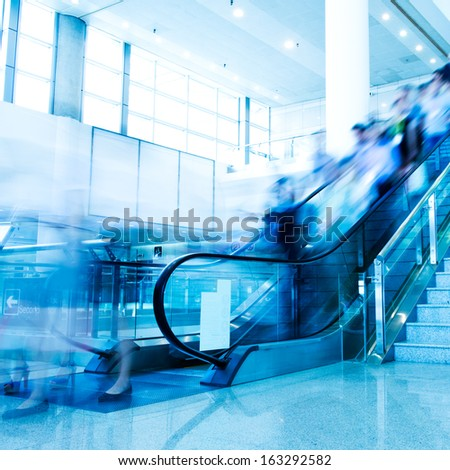 Group of businesspeople moving down on escalator in office. blurred motion. - stock photo