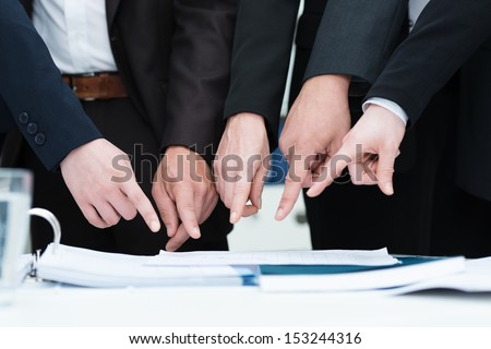 Group of businesspeople pointing to a document on a desk, close up cropped view of their hands