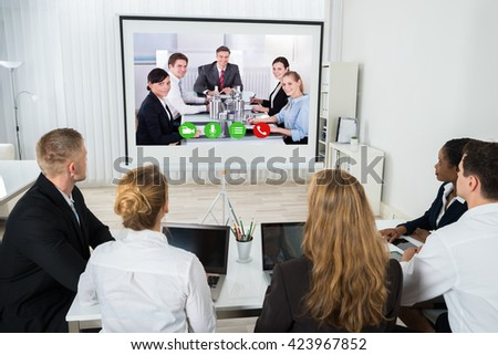 Group Of Businesspeople Together Videoconferencing At Workplace - stock photo