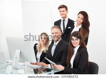 Group of businesspeople using desktop PC together in office