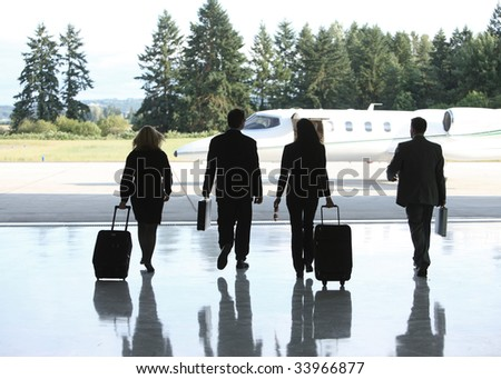 Group of businesspeople walking to corporate jet - stock photo