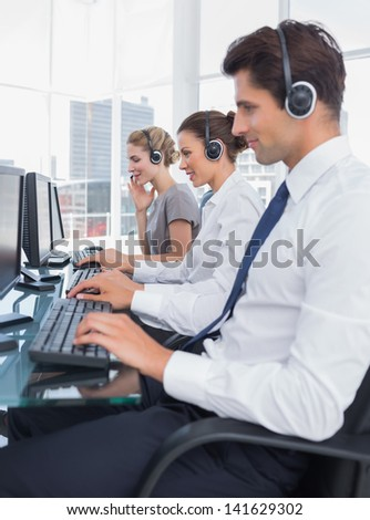 Group of call center employees working in line in a bright office - stock photo