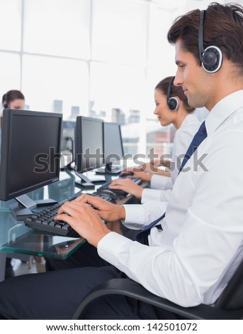 Group of call center employees working on computers in a bright office