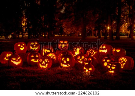 Group of candle lit carved Halloween pumpkins in park on fall evening - stock photo