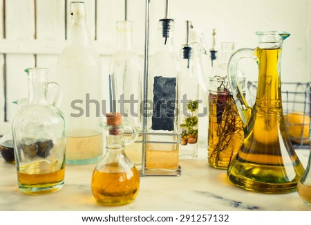 Group of Carafe, decantres and bottles of various oil on the marble kitchen table. Country rustic style.  - stock photo