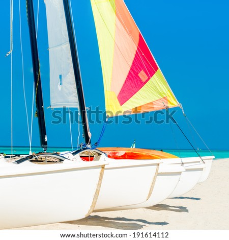Group of catamarans with colorful sails on a tropical beach in Cuba - stock photo
