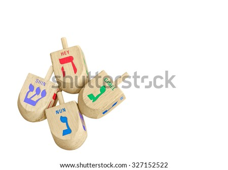 Group of Chanukah wooden dreidels isolated on white background, top down view. 4 large wood dreidels with colorful Hebrew letters nun, gimel, hey, shin. Copyspace.   - stock photo