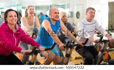 Group of  cheerful adult people training in sport club on fitness cycle. Selective focus on man
