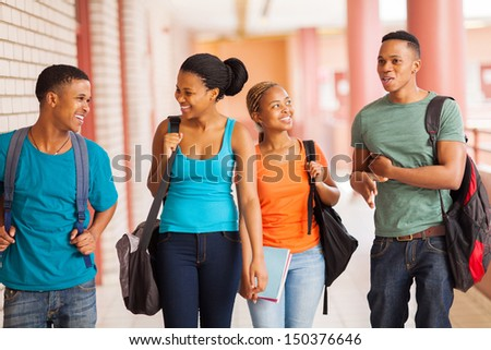 group of cheerful african college students walking in building corridor - stock photo