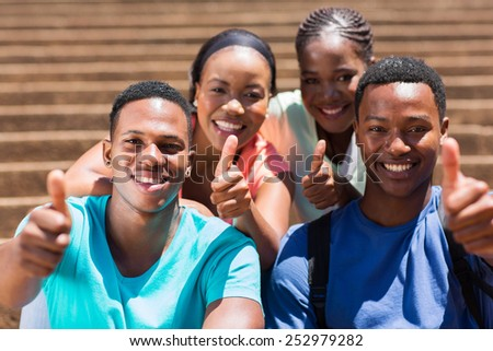 group of cheerful african friends giving thumbs up - stock photo