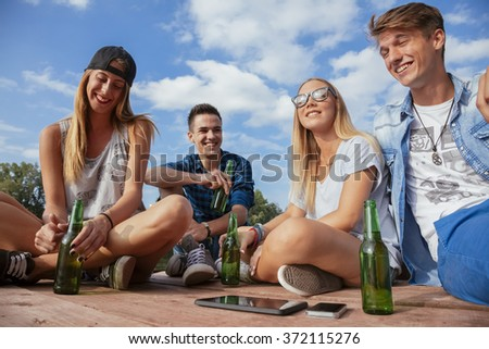 Group Of Cheerful Friends Chilling Near Lake - stock photo