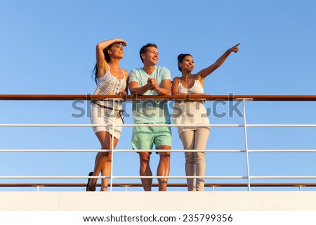 group of cheerful friends enjoying sunset on cruise - stock photo