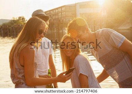 Group Of Cheerful Friends Having Fun Near Lake Using Smart Phone - stock photo