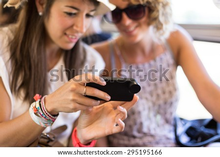 Group Of Cheerful Friends Having Fun Using Smart Phone
