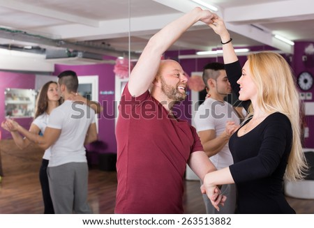 Group of cheerful happy young adults dancing salsa in club - stock photo