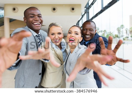 group of cheerful multiracial businesspeople reaching for the camera - stock photo