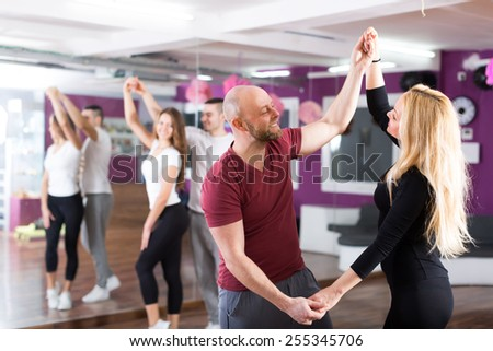 Group of cheerful smiling young adults dancing salsa in club - stock photo