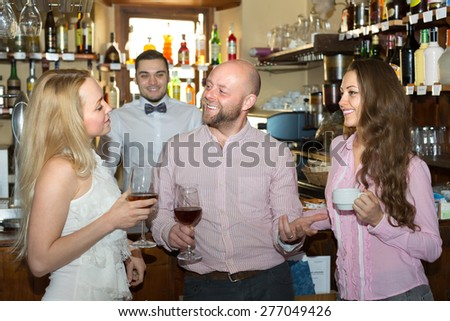 Group of cheerful smiling young adults hanging out in bar with drinks - stock photo