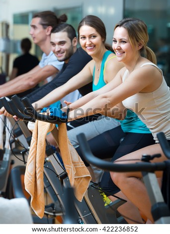 Group of cheerful smiling young adults working out of cycling in modern fitness club