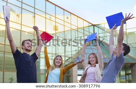 Group of cheerful student show education success raising hands up with folders - stock photo